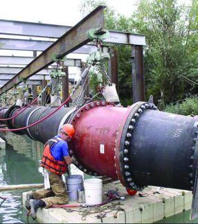 Man working on a large pipe on a floating work platform