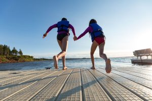 Girls holding hands to jump off dock