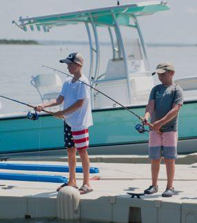 Boys fishing off of boat dock