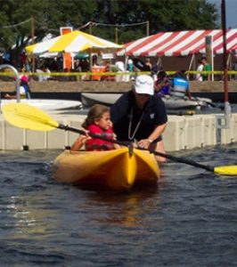 Child being guide in a kayak from a dock