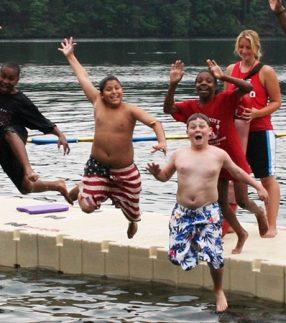 Kids jumping into water off of floating swim platform